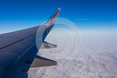 DUBLIN, IRELAND - APRIL 23, 2017: Ryanair logo in the wing of the airplane with sky as the background. Ryanair has cheap flights
