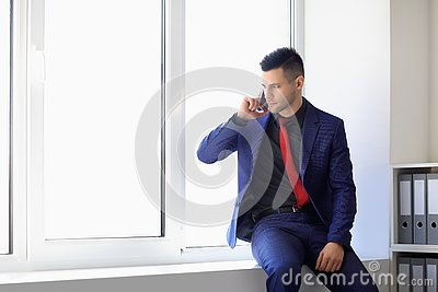 Serious business man talking on cell phone sitting on window sill