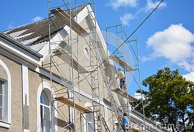 Contractors plastering house facade outdoor. Painting and plastering exterior house scaffolding wall with asbestos roof repair