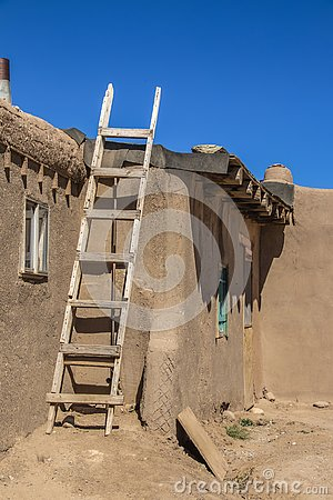 Homemade wooden ladder against side of mud adobe pueblo house where tar paper is being put on roof - with dramatic shadows under