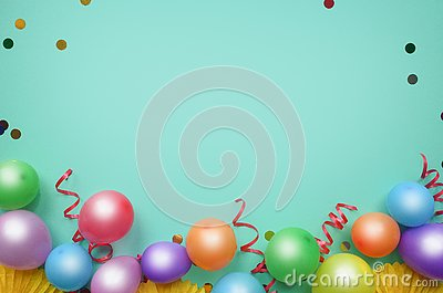 Colorful balloons and confetti on turquoise table top view. Birthday, holiday or party background. Flat lay style. Empty space for