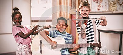stock image of portrait of children playing musical instruments in classroom