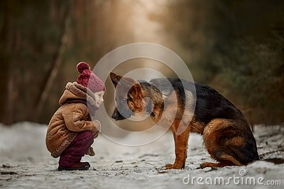 Little girl with German shepherd 6-th months puppy at early spring