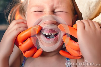 The doctor is trying to see the mouth of a little girl with an orthodontic appliance and crooked teeth