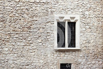 Old stone wall and cement with old window. Stone background. Krakow stone wall. Griddles on the windows. Krakow building