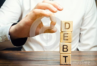 Businessman removes wooden blocks with the word Debt. Reduction or restructuring of debt. Bankruptcy announcement. Refusal to pay