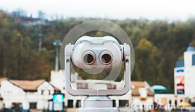 Touristic telescope look at the city with view snow mountains, closeup metal binocular on background viewpoint observe vision