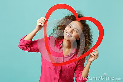 Portrait of beautiful african girl in casual clothes holding big red wooden heart isolated on blue turquoise wall