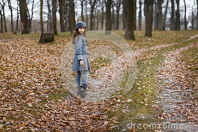 A cute little girl in grey coat and gray hat near the thick old oak in the oak wood at the sunset