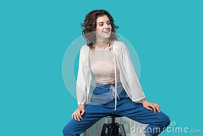 Portrait of happy successful satisfied beautiful young brunette woman in casual style sitting on chair, toothy smiling and looking
