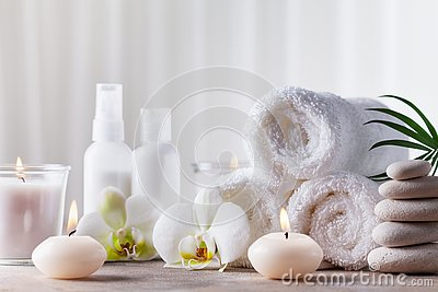 Aromatherapy, spa, beauty treatment and wellness background with massage pebbles, orchid flowers, towels, cosmetic products