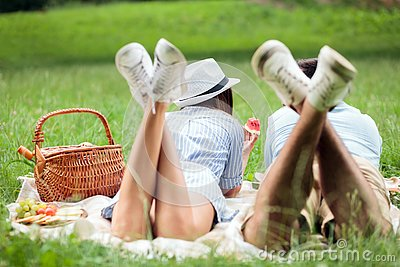 stock image of happy young couple lying next to each other and eating watermelons, picnic in a park. view from behind