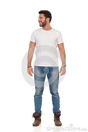 Smiling Man In Jeans And White T-shirt Is Standing And Looking Away. Front View