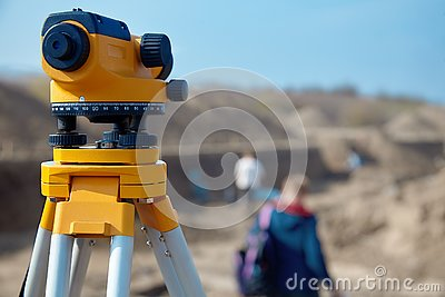 Special device level for surveyor builders, geodesy equipment close up in front of a ground work with people on blurred backgrou