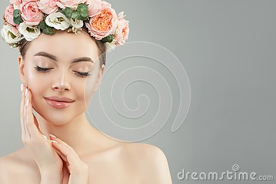 Beautiful woman touching her face her hand. Pretty candid girl with flowers. Facial treatment, face lifting, anti aging