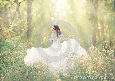 Elegant and tender girl with black hair in white elegant light dress, lady runs in forest, turning pretty face on camera