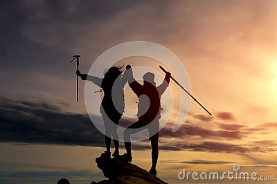 stock image of male and female hikers climbing up mountain cliff and one of them giving helping hand