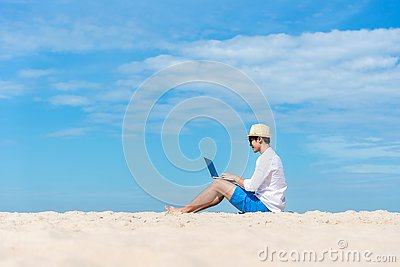 Lifestyle young asian man working on laptop while sitting chill on the beautiful beach, freelance working social on holiday summer