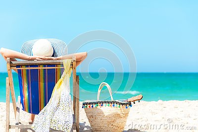 Summer Vacation. Asian lifestyle healthy woman relaxing and happy on beach chair with cocktail coconut juice in holiday summer.  C