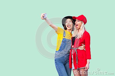 Couple of beautiful stilysh hipster best friends in fashionable clothes hugging with love, posing for camera and making selfie or