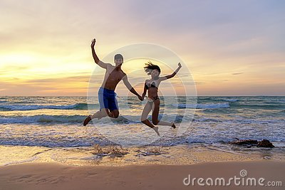 Summer Vacation.  Couple jumping holding hands on tropical on the beach sunset time in holiday trips.  Honeymoon holidays people r