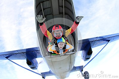 Tandem skydiving. Active woman are jumping out of a plane.