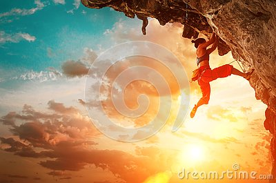 Athletic Woman climbing on overhanging cliff rock with sunset sky background