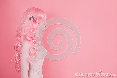 Pink hair woman in wig on pastel background. Beautiful sexy girl in long wavy wig. Minimal spring trend. Pastel color design. 2019