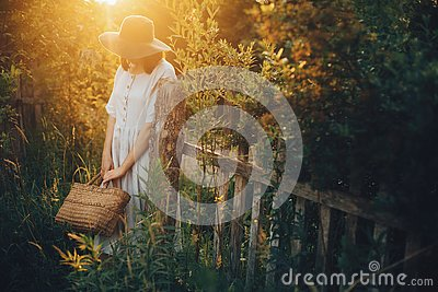 Stylish girl in linen dress holding rustic straw basket at wooden fence  in sunset light. Boho woman relaxing and posing in summer