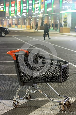 stock image of shopping mall parking lot and empty shopping cart