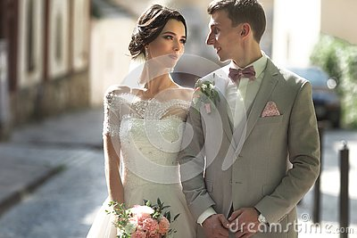 A loving couple of newlyweds walks in the city, and smile. The bride in a beautiful dress, the groom dressed stylishly
