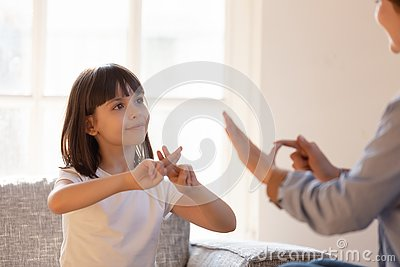 Mother daughter sitting on couch nonverbal communicating with sign language