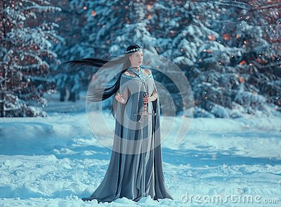Charming attractive lady in snowy forest, militant elf princess with black long flying hair holds sword, loose gray warm