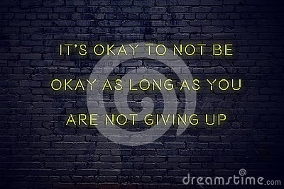 Positive inspiring quote on neon sign against brick wall its okay to not be okay as long as you are not giving up