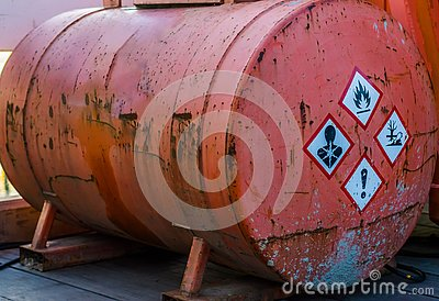 Old rusty silo tank containing hazardous substances, warning labels on the side, storage of dangerous liquids