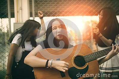 stock image of group of asian teenager standing outdoor plying spanish guitar and dancing with happiness emotion