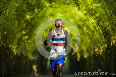 Young athletic and attractive black afro American runner man doing running workout training outdoors on urban city park in fitness