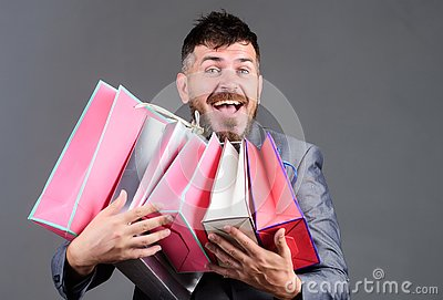 Exclusive commercial offer. Man bearded businessman customer carry many shopping bags. Enjoy shopping profitable deals