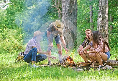 Company friends prepare roasted marshmallows snack nature background. Camping activity. Company youth camping forest