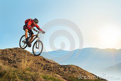 Cyclist in Red Riding the Bike Down the Rock at Sunrise. Extreme Sport and Enduro Biking Concept.