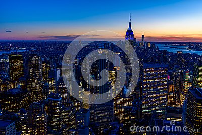 New York City skyline at night - skyscrapers of midtown Manhattan with Empire State Building at Amazing Sunset - USA