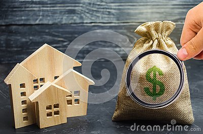A bag with money and wooden houses. Selling a house. Apartment purchase. Real estate market. Rental housing for rent. Home prices