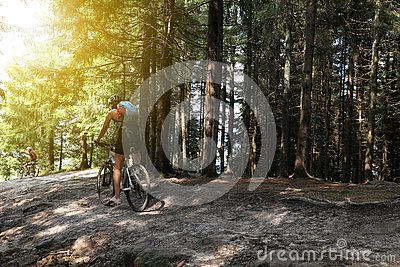 Group of cyclists riding bikes down forest