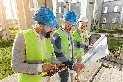 Mixed group of young architects and civil engineers or business partners meeting on a large construction site