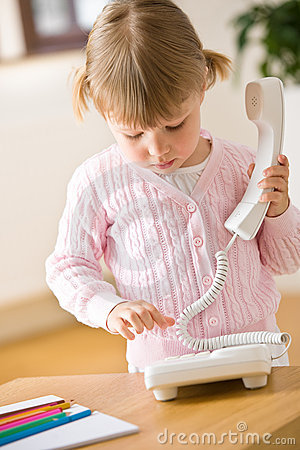 Little girl dial number on phone in lounge
