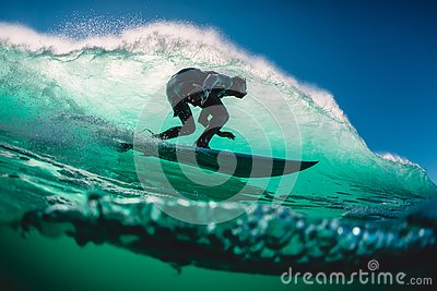 stock image of april 18, 2019. bali, indonesia. surfer ride on barrel wave. professional surfing at big waves in padang padang