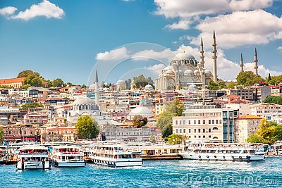 Touristic sightseeing ships in Golden Horn bay of Istanbul and view on Suleymaniye mosque with Sultanahmet district against blue