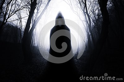Hooded ghost in haunted forest with fog on Halloween night