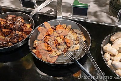 Grilled Eryngi mushroom and carrot in fry pan. Detail of buffet served in line