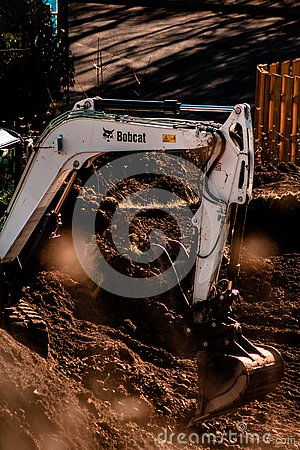 Bobcat Tractor Digging up Earth to build Houses